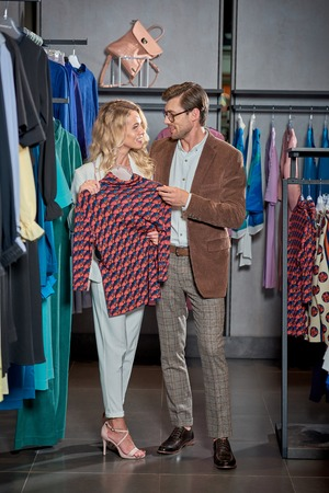 Young couple smiling each other while shopping together in boutique Foto de archivo - 111533969