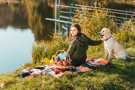 Selective focus of young woman siting on blanket with adorable golden retriever near pond in park