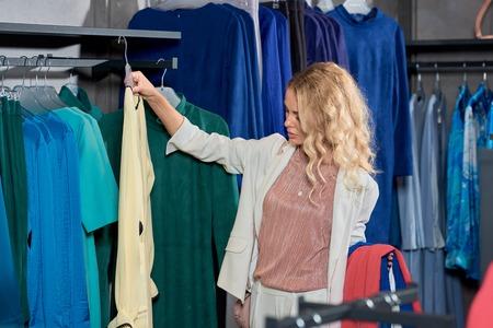 Attractive young woman choosing clothes in boutique Foto de archivo - 111534310