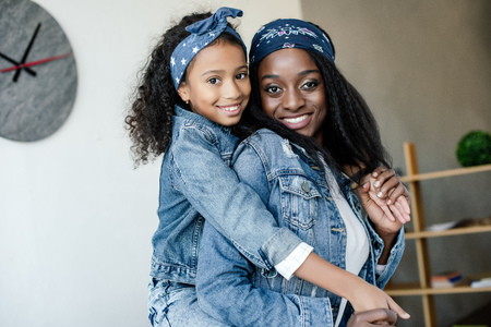 Cute African American kid hugging smiling mother in similar clothing at home 写真素材