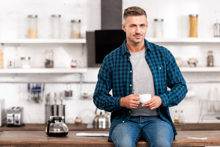 Handsome man in checkered shirt holding cup of coffee and looking at camera in kitchen 版權商用圖片