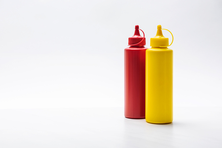 Close-up shot of bottles of ketchup and mustard on white surface