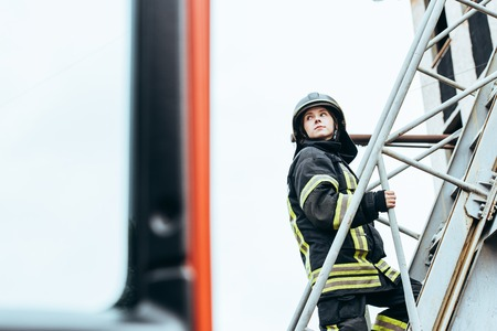 Female firefighter in protective uniform and helmet standing on ladder on street
