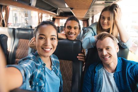 Selectieve focus van lachende Aziatische vrouw die selfie neemt met multiculturele vrienden in reisbus