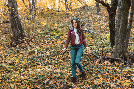 Fashionable young woman in leather jacket and beret walking down in autumnal park Stock Photo