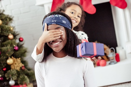 Smiling African American daughter gifting Christmas present to mother and closing her eyes for surprise at home Stock Photo