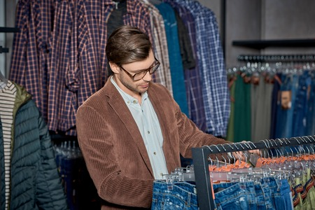 Handsome young man in eyeglasses choosing stylish clothes in boutique Foto de archivo - 111561703
