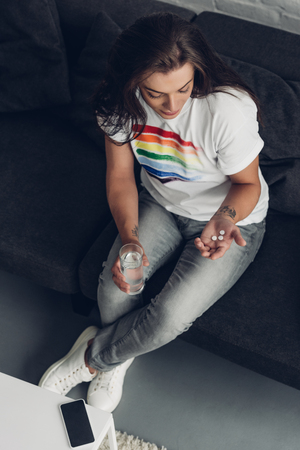 High angle view of depressed young transgender man with pills and glass of water sitting on couch Stock Photo