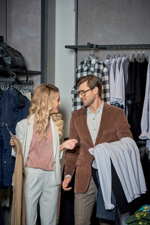 Couple holding fashionable clothes and smiling each other in store Foto de archivo - 111561651