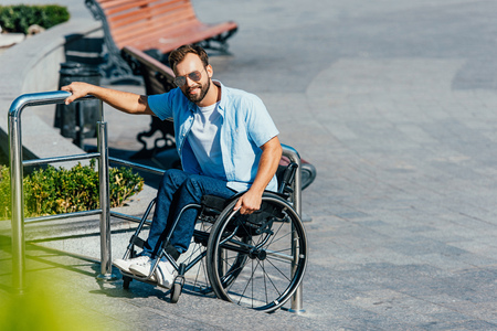 Handsome man in sunglasses using wheelchair on stairs without ramp and looking at camera