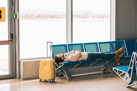 Young man sleeping on seats while waiting for flight in airport terminal 스톡 콘텐츠 - 111561824