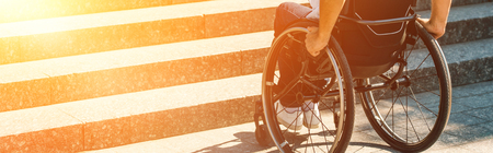 Cropped image of disabled man using wheelchair on street and stopping near stairs without ramp Stockfoto