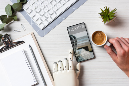 Partial view of businessman with prosthesis arm using smartphone with tickets on screen at table with coffee cup in office Stock Photo
