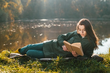 Attractive young woman reading book while laying on blanket near pond in park Banco de Imagens