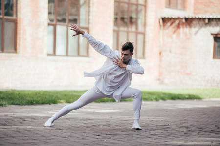 Handsome young man dancer in white clothes dancing on urban city street Foto de archivo - 111561886