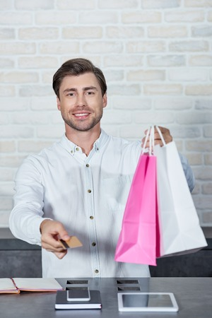 Smiling young salesman holding paper bags and credit card in shop Imagens