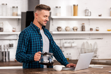 Smiling man holding coffee pot and using laptop at home