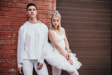 Couple of young dancers in white clothes standing together near brick wall on street Foto de archivo - 111562028