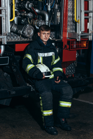 Male firefighter in uniform with helmet looking at camera at truck at fire station Reklamní fotografie