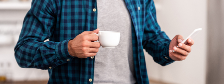 Mid section of man in checkered shirt holding cup of coffee and using smartphone at home 版權商用圖片