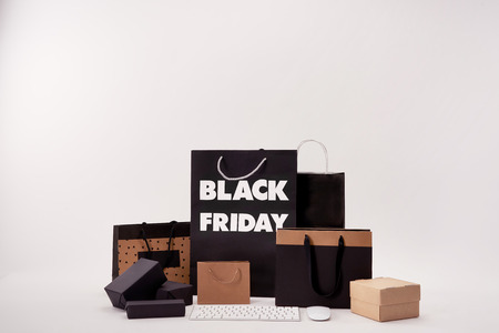 Computer keyboard with mouse and various boxes with shopping bags with black Friday sign on white