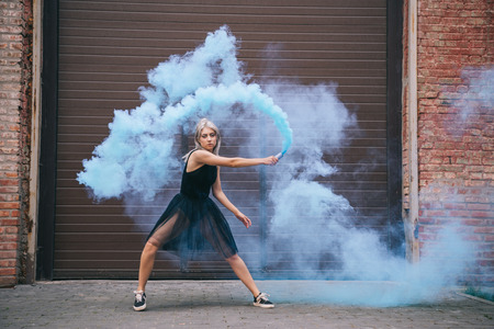 Attractive girl looking at camera and dancing in blue smoke on street Imagens