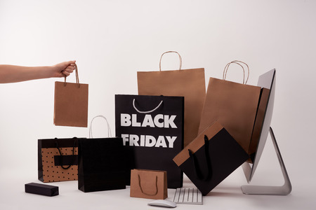 Cropped shot of woman with different boxes with shopping bags near computer on white background