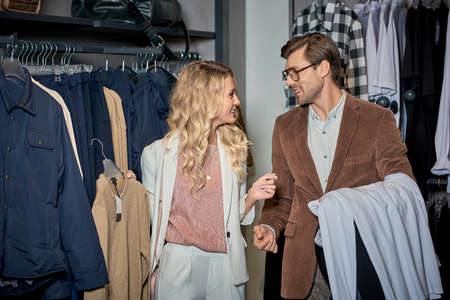 Couple holding stylish clothes and smiling each other in boutique Foto de archivo - 111562480