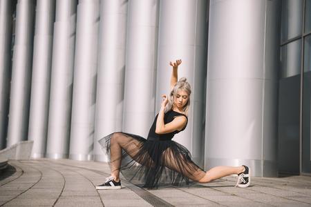 Beautiful young ballerina in black skirt dancing on street Stock Photo