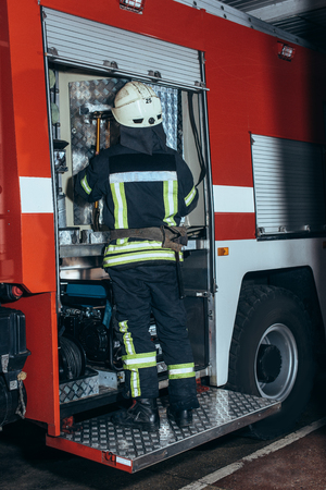 Back view of firefighter in fireproof uniform and helmet standing near truck at fire station