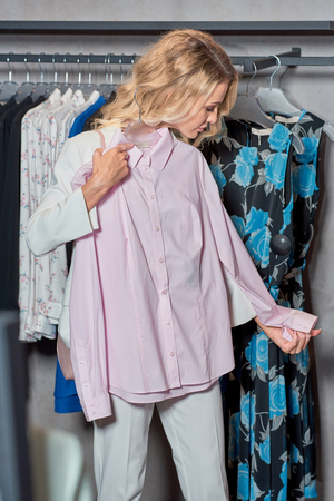 Attractive woman holding hanger with fashionable shirt in boutique Foto de archivo - 111562491