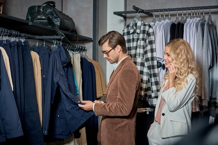 Smiling young woman looking at handsome man choosing clothes in store Foto de archivo - 111562875