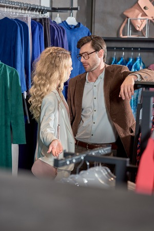 Young man and woman looking at each other while shopping together in boutique Foto de archivo - 111562731