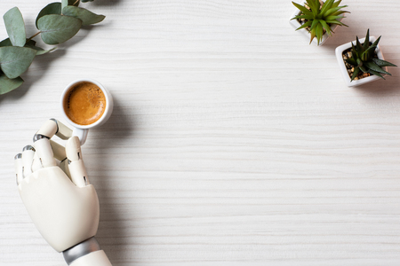 Partial view of cyborg hand sitting at table with coffee cup and plants in office