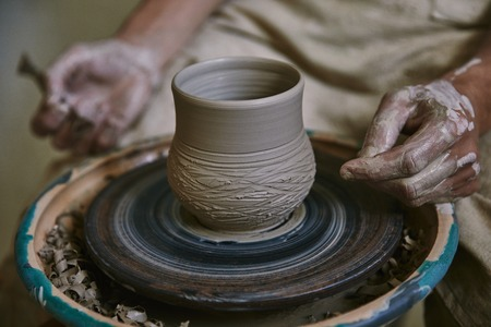 Cropped image of male craftsman working on potters wheel at workshop Imagens