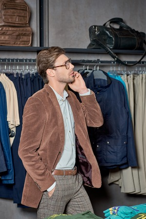 Handsome man talking by smartphone and looking away while shopping in boutique Foto de archivo - 111563041