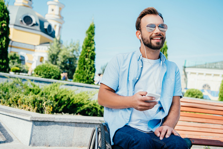Smiling handsome man in wheelchair holding smartphone and listening to music on street, looking away Stock Photo