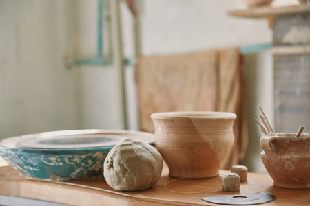 Selective focus of clay and pottery tools at table in workshop Banco de Imagens - 111563056