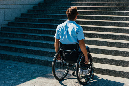 Back view of man using wheelchair on street and looking at stairs without ramp Stock Photo