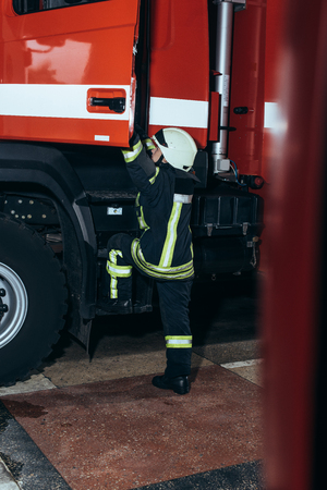Female firefighter in protective uniform getting into truck at fire station
