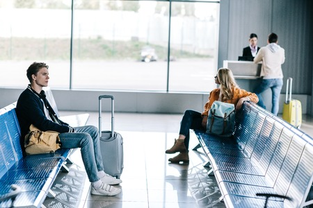 Young people with luggage sitting and waiting for flight in airport terminal