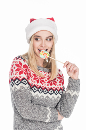 Portrait of beautiful woman in sweater and Santa Claus hat with lollipop isolated on white background Stock Photo