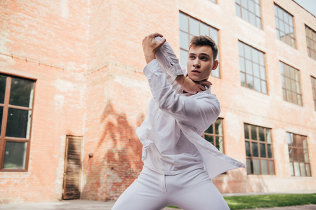 Young man in white clothes dancing on city street