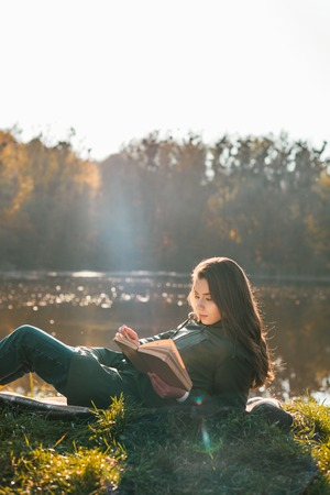 Attractive girl laying on blanket and reading book near pond in park Imagens