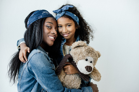 Portrait of smiling African American daughter with teddy bear hugging mother at home