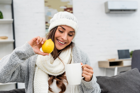 Smiling young woman in warm clothes holding lemon and cup of tea at home