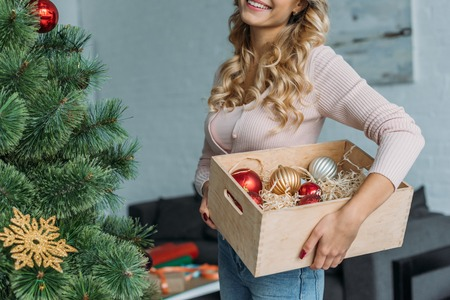 Cropped image of girl decorating Christmas tree and holding box with baubles at home