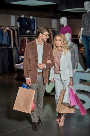Smiling stylish couple holding shopping bags in boutique Foto de archivo - 111569443
