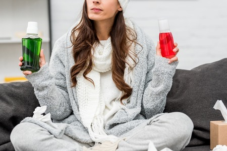 Cropped shot of sick young woman in warm clothes choosing between red and green bottles of gargling liquids at home