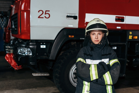 Portrait of female firefighter in helmet with arms crossed standing at fire station with truck behind